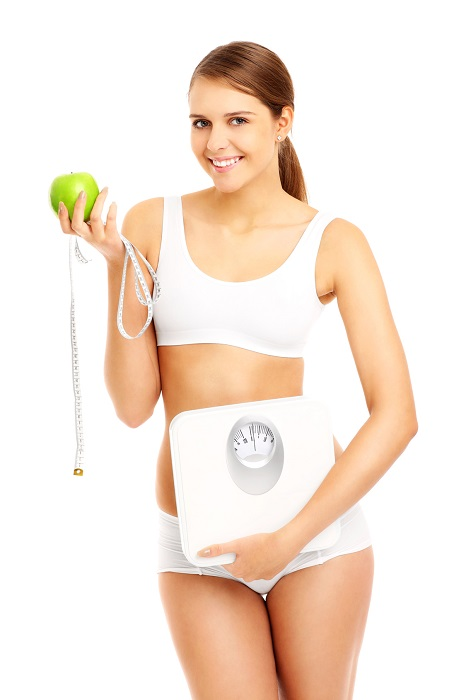 Fit woman with apple tape and scales