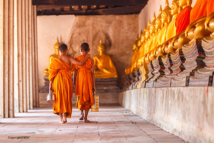 Two novices walking return and talking in old temple at sunset t