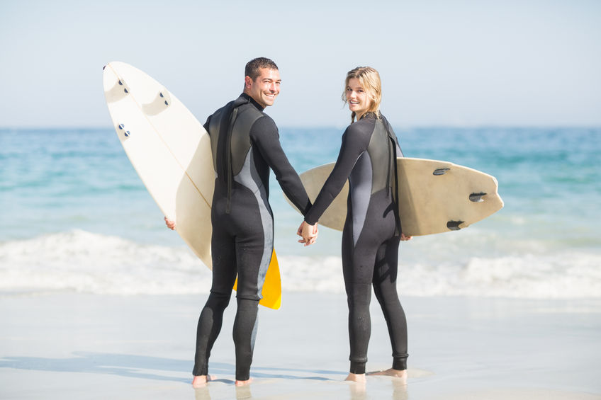 54487365 - couple with surfboard holding hand on the beach on a sunny day