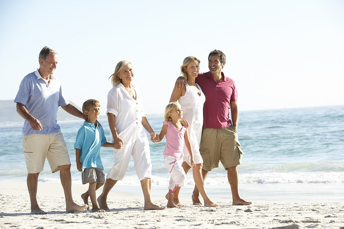 Three Generation Family On Holiday Walking On Beach (1)