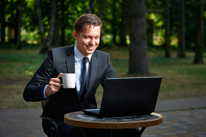 Handsome smiling businessman holding coffee cup in the park cafe