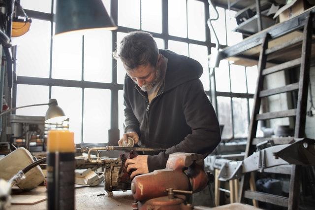 focused-male-mechanic-using-spray-paint-on-metal-detail-3822927