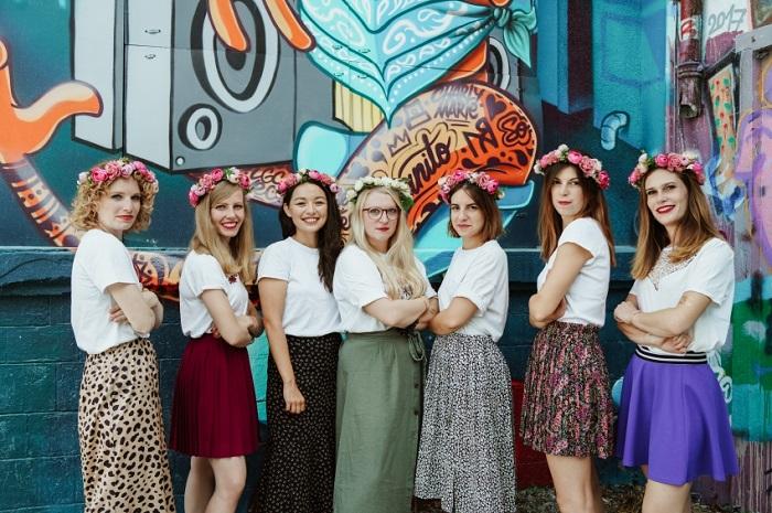 jeunes-femmes-avec-couronne-de-fleur-bras-coirses-devant-des-graffitis