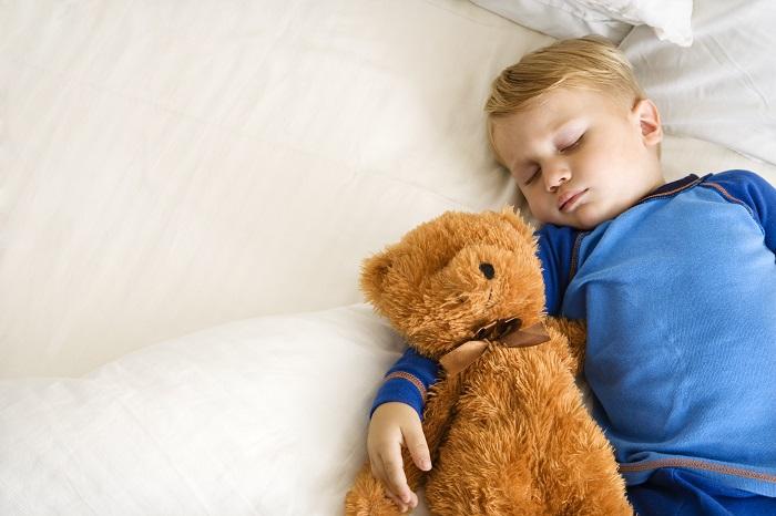 Child sleeping with bear.