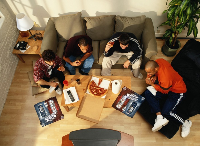 Above View of Four Men Eating Pizza